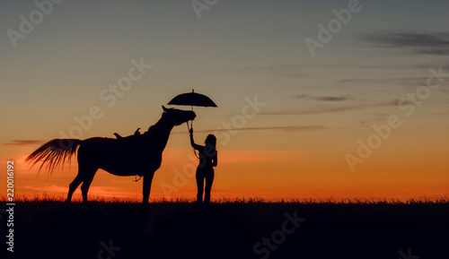 Cuadros en Lienzo Curious horse and girl with open umbrella on romantic sunset