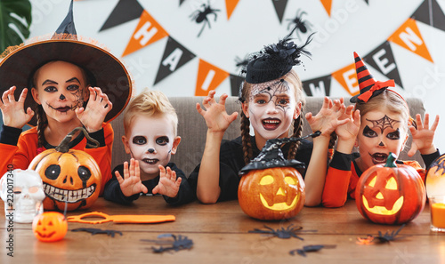 happy Halloween! a group of children in suits and with pumpkins in home