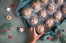 Child's Hand Taking A Blueberry Muffin With Sugar Icing From A Baking Tray With Christmas Decorations