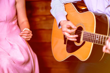 Golden Blues. Man's Male Hands Playing The Guitar, Singer Solo Vocal Woman With Music Notation Stand On Wooden Background, Acoustic Guitar With Nature Light. Concept Of Jazz Band Performing On Events