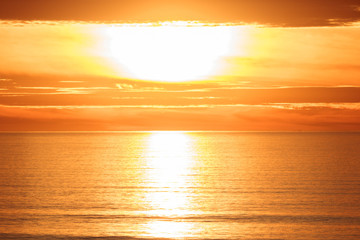 Bright golden dramatic sunset sun reflecting orange, gold, off calm ocean