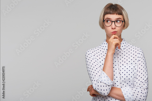 Portrait of pensive thoughtful blonde young woman wears polka dot shirt and glas Canvas Print