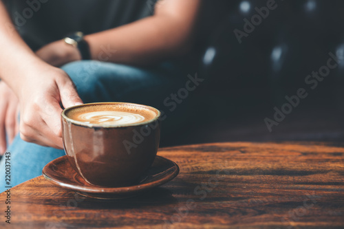 Closeup image of a woman holding a cup coffee on vintage wooden table in cafe