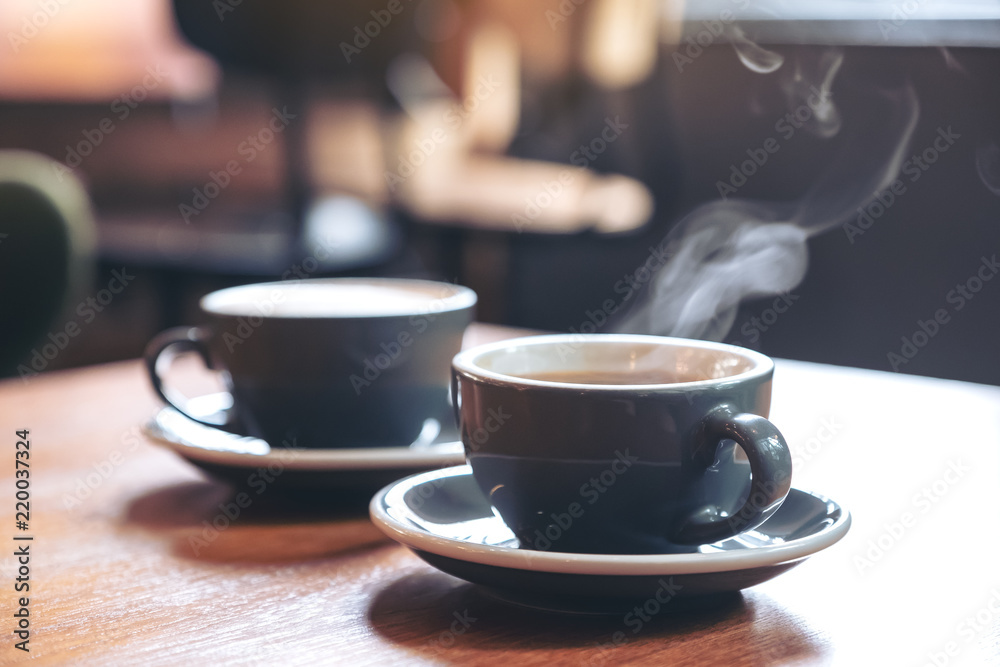 Fototapeta Closeup image of two blue cups of hot latte coffee and Americano coffee on vintage wooden table in cafe