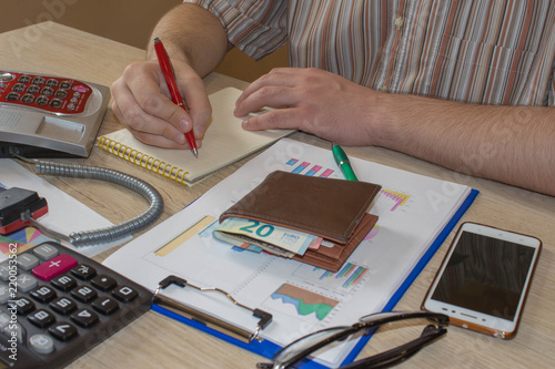 Stock market table analysis, calculator and pen indicates research and analysis, with cash. analysis of the annual budget with calculator and money on the table
