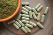 Leinwandbild Motiv Supplement kratom green capsules and powder on brown plate. Herbal product alt-medicine kratom is  opioid. Home alternative pain remedy, opioid addiction, dangerous painkiller, overdose.