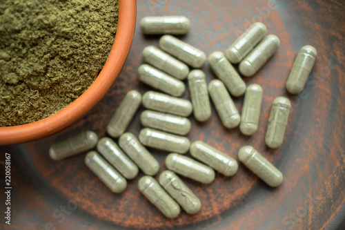 Stampa su Tela  Supplement kratom green capsules and powder on brown plate