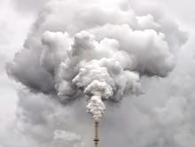Smoke From Factory Pipe Against Dark Overcast Sky
