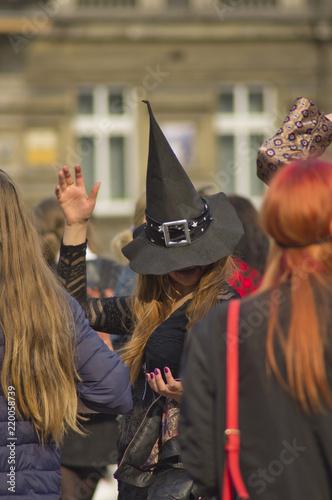 Naklejka premium wróżka w kapeluszu gestem ręki zaczarowuje dwie kobiety