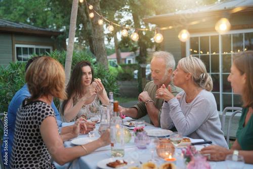 Friends enjoying summer barbecue dinner in garden Canvas Print