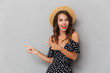 Cute woman wearing hat pointing over grey wall.