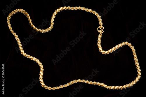 Foto Golden chain on a dark pattern