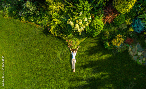 top view portrait of a pretty young woman relaxing on a grass #220069790