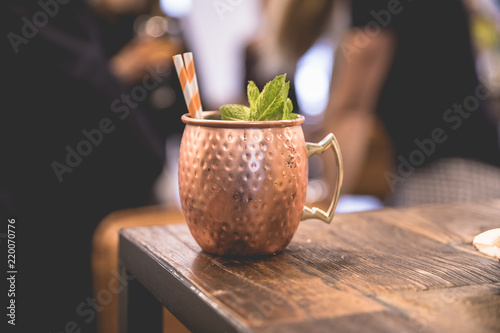 Valokuva  Close up on a copper cup with Moscow Mule cocktail, fresh mint as decoration and