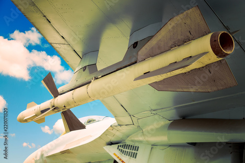 фотография  Rocket missile of fighter jet airplane over blue sky with clouds