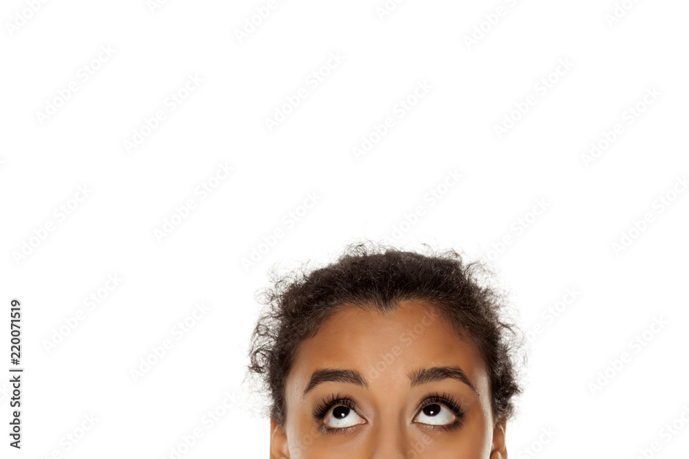 Fototapeta half portrait of a young dark skinned girl looking up on white background