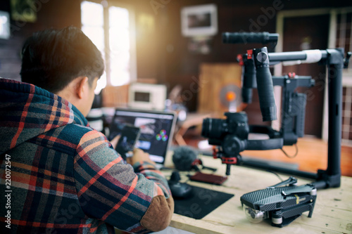 Fotografie, Obraz  Young freelancer man editing video on laptop and checking smartphone for uploading video to internet online or social media