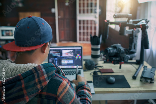 Fototapeta  Young freelancer man editing video on laptop for uploading video to internet online or social media