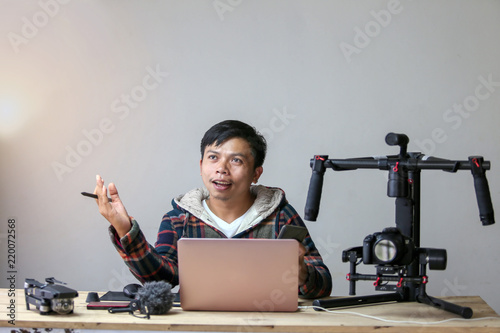Fotografia, Obraz Asia young man creative cheerful present by project production filmarking or vlog travel, This is lifestyle of creative producer freelance with a laptop and stabilizer camera