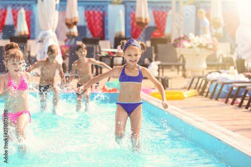 Cute children playing in swimming pool on summer day Wallpaper Mural