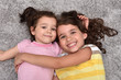 Two cute smiling sisters hugging each other lying on the carpet and looking at the camera. Top view.