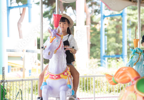 Tuinposter Amusementspark メリーゴーランドに乗る子供