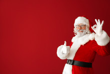 Portrait Of Santa Claus Showing Thumb-up And OK Gesture On Color Background