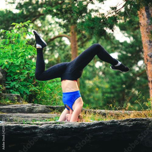 Valokuva Blonde woman doing headstand on a rock in the forest