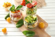 Delicious vegetable salads in mason jars on wooden board