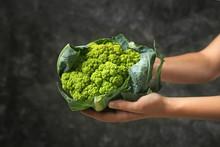 Woman Holding Green Cauliflower On Dark Background