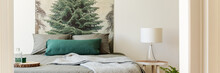 Real Photo Of Bedside Table With Glass Lamp Standing By The Double Bed With Grey Bedclothes In Bright Bedroom Interior With Forest Tree Poster