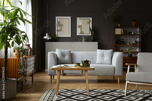 Photo  Wooden table and armchair on patterned carpet in retro flat interior with grey sofa and posters