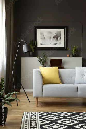 Photo  Yellow cushion on grey sofa next to lamp in scandi living room interior with poster