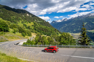 Red car on a road through switzerland alps. Curvy road in mountains. Travelin...