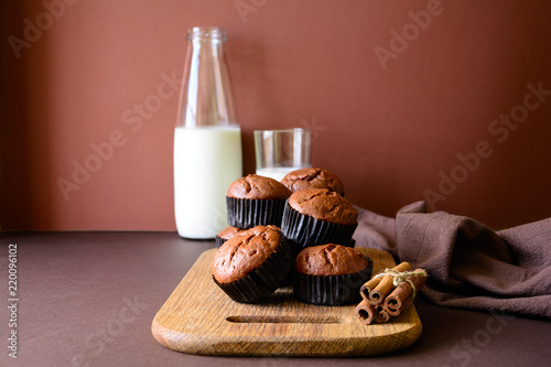 Homemade chocolate muffins (brownies) with cinnamon and milk on brown paper background