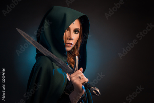 mysterious-young-woman-keeping-sharp-knife-wearing-green-cape-with-a-hood
