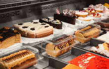 Refrigerated Display Case With Delicious Desserts In Supermarket