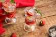 Glass cups of fresh strawberry mojito on wooden table