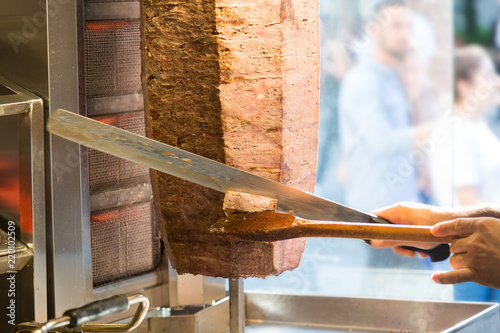 Cutting with doner knife traditional turkish Doner Kebab meat. Turkish cuisine street food in Istanbul, Turkey.