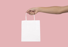 Hand Holding Blank White Paper Bag For Mockup Template Advertising And Branding Isolated On Pink Background.