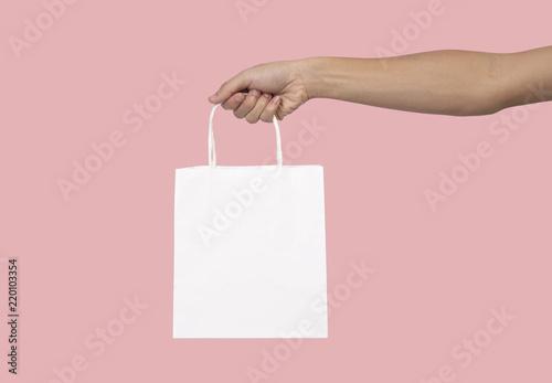 Hand holding blank white paper bag for mockup template advertising and branding isolated on pink background Billede på lærred