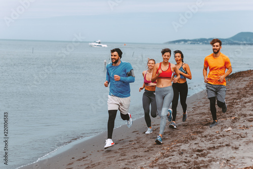 In de dag Jogging Group of young sports people running on the beach by the sea
