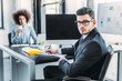 handsome businessman looking at camera in office