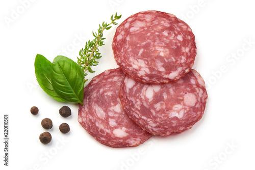 Fototapeta Sliced salami smoked sausage, basil leaves and peppercorns, isolated on white background. obraz
