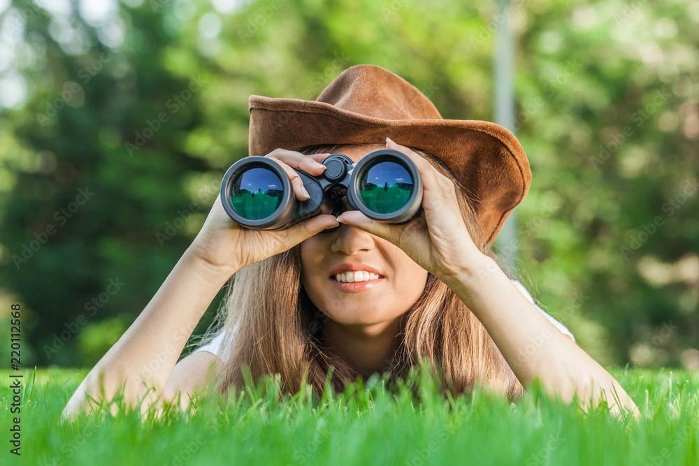 Fototapety, obrazy: Portrait of a Woman Using Binoculars in a Park