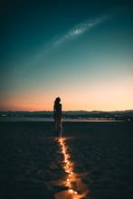 Sagoma Di Una Ragazza Guarda Felice Il Cielo Notturno Con La Via Lattea E Le Stelle Cadenti Prima Di Esprimere Un Desiderio Su Una Spiaggia Deserta, Poco Dopo Il Tramonto Con La Striscia Luci Led.