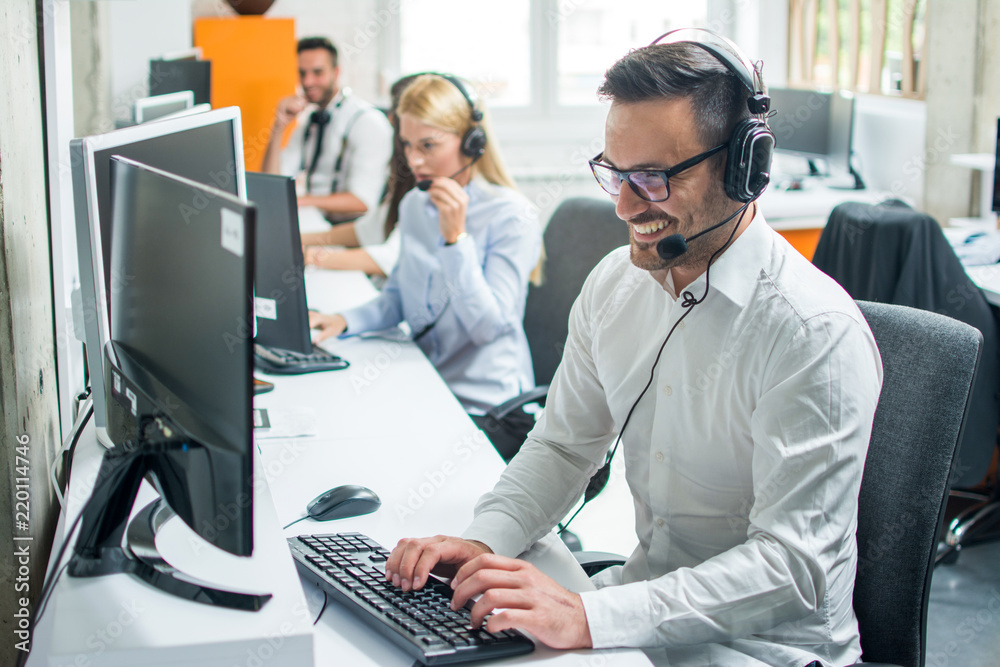 Fototapeta Young male technical support dispatcher with headset talking with customer in call center