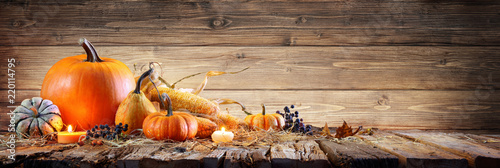 Fototapeta Thanksgiving Background - Pumpkins With Corncob And Candles On Rustic Wooden Table