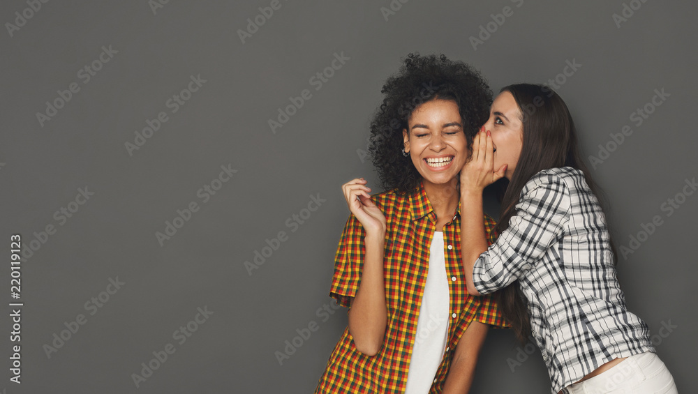 Fototapety, obrazy: Young woman whispering to her friend against grey background