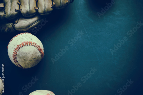 Baseball ball with glove on dark background with grunge texture, old and used from sport game Wallpaper Mural